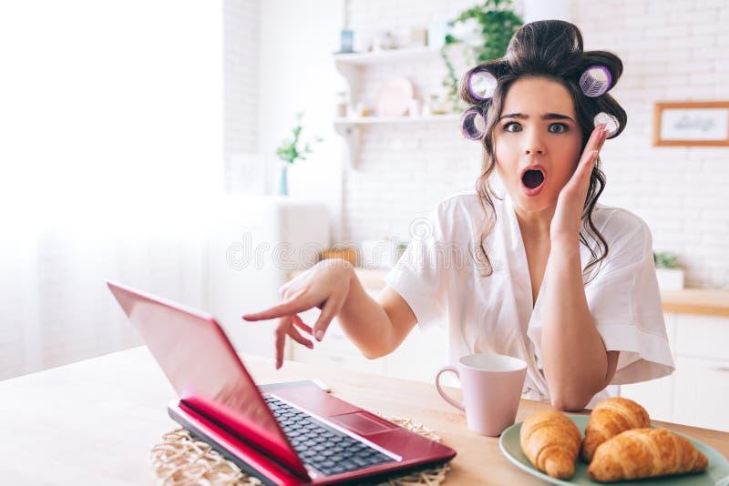 在膝上型计算机的情感惊奇年轻在照相机的womanpoint和神色 站立在厨房里 张的嘴 新月形面包和杯子 库存照片