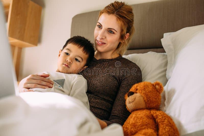 在膝上型计算机的母亲和儿子观看的动画片一起 库存照片