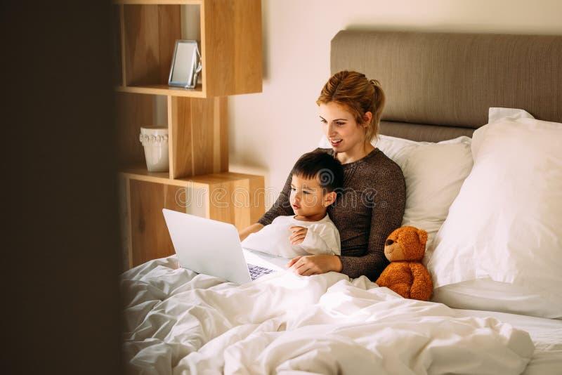 在膝上型计算机的母亲和儿子观看的动画片在床上 免版税库存照片
