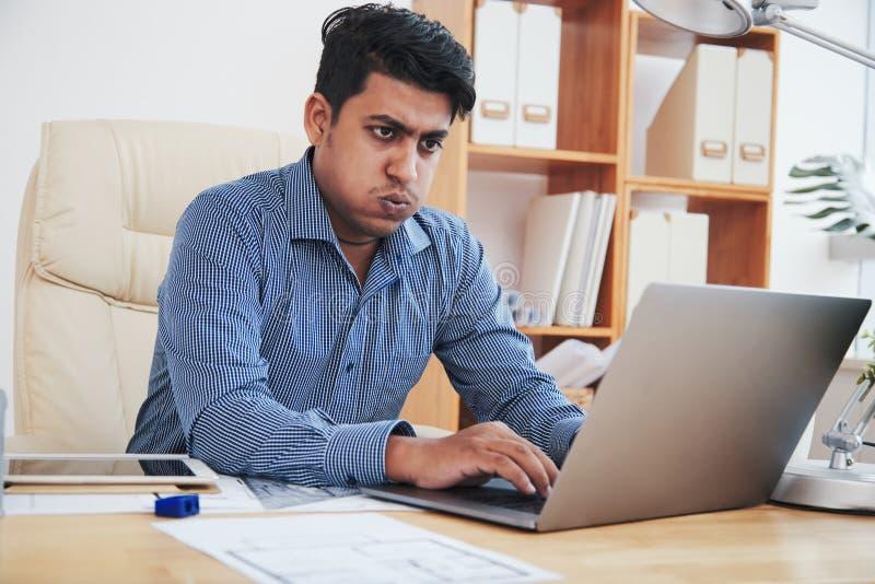 在膝上型计算机的疲乏的商人 库存照片
