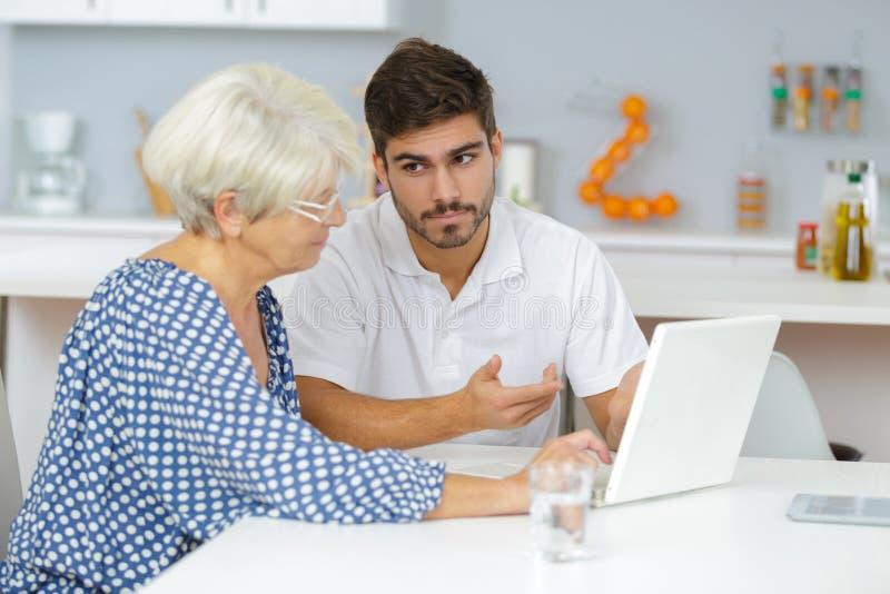 在膝上型计算机的祖母和孙子观看的家庭图片 库存图片