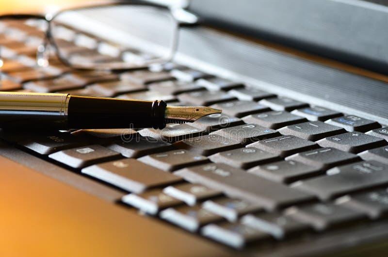 在膝上型计算机的笔和放大镜 免版税库存照片