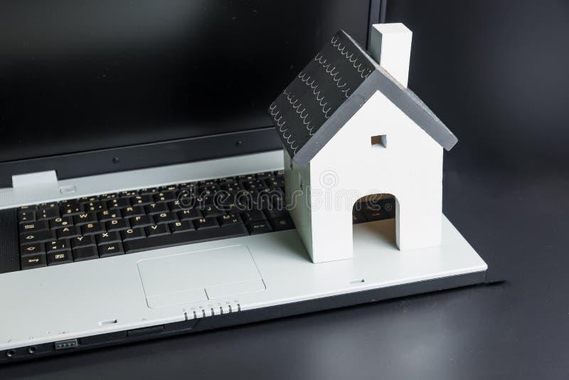 在膝上型计算机笔记本的木白色水管模型 E 不动产概念,新房概念 买房子 库存照片