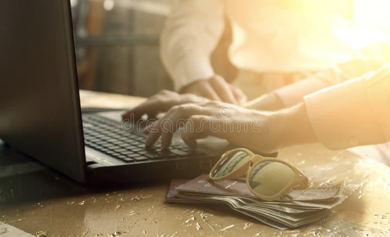 在膝上型计算机键盘的人的手,妇女在背景中,金钱在护照和太阳镜投资了 ??  免版税库存图片