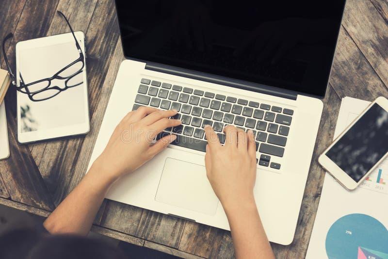在膝上型计算机键盘的女性手有另一种计算机片剂的 免版税库存照片