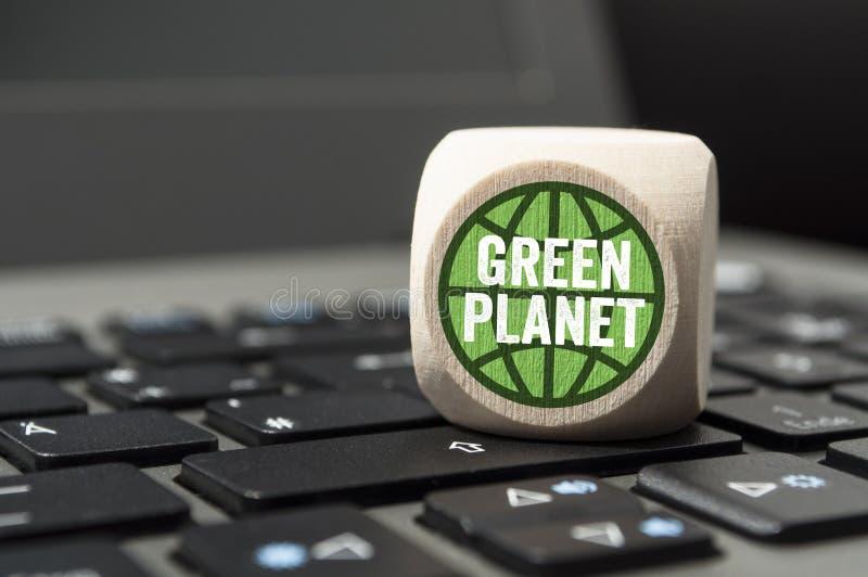 在膝上型计算机键盘的立方体有绿色行星的 免版税库存图片