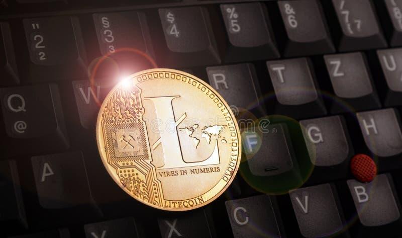 在膝上型计算机键盘的金黄litecoin国际航空测量中心硬币 图库摄影