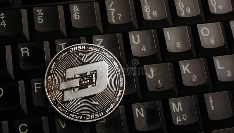 在膝上型计算机键盘的银色破折号硬币 免版税库存照片