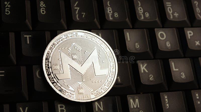 在膝上型计算机键盘的银色Monero XMR硬币 免版税库存图片