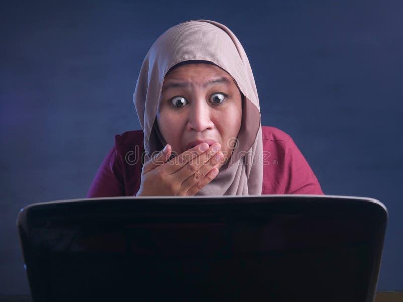在膝上型计算机震惊震惊姿态的回教女实业家工作 免版税库存照片