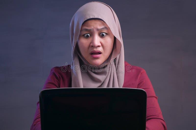 在膝上型计算机震惊震惊姿态的回教女实业家工作 库存照片