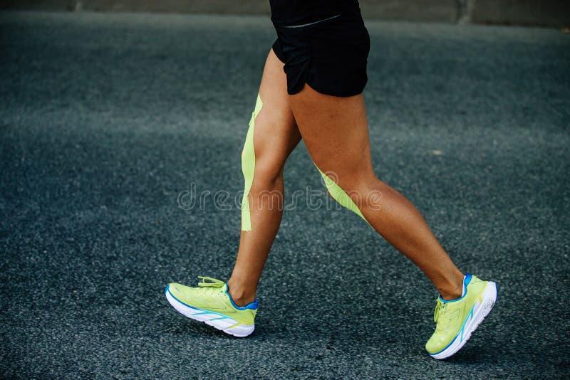 在膝盖女性赛跑者的kinesio磁带 库存图片