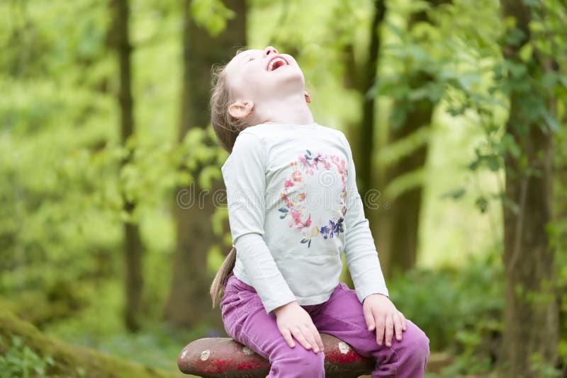 在膝盖的少女坐的笑的手在森林地森林里 库存图片