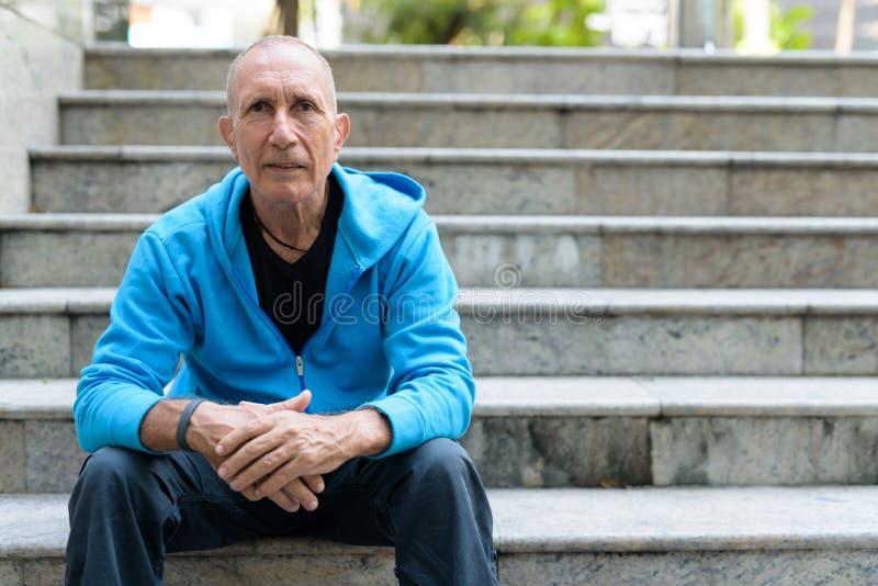 在膝盖的秃头老人倾斜的胳膊,当坐台阶时 免版税库存照片