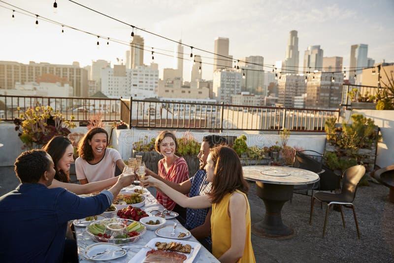 在膳食的屋顶大阳台会集的朋友与城市地平线在背景中 免版税库存照片