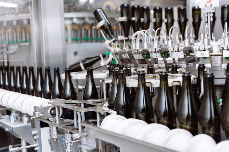 在自动传动机线的玻璃瓶在香槟或酒工厂 装瓶的酒精饮料植物 库存照片