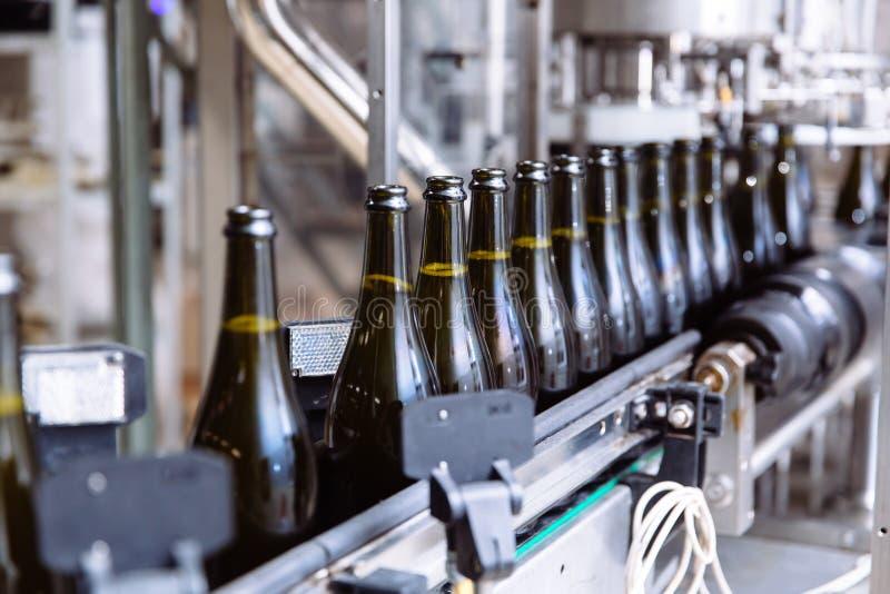 在自动传动机线的玻璃瓶在香槟或酒工厂 装瓶的酒精饮料植物 免版税库存照片