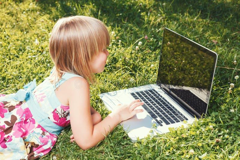 在自我隔离期间使用笔记本电脑在家学习的儿童 库存图片