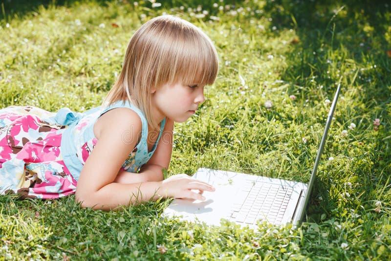 在自我隔离期间使用笔记本电脑在家学习的儿童 免版税库存照片