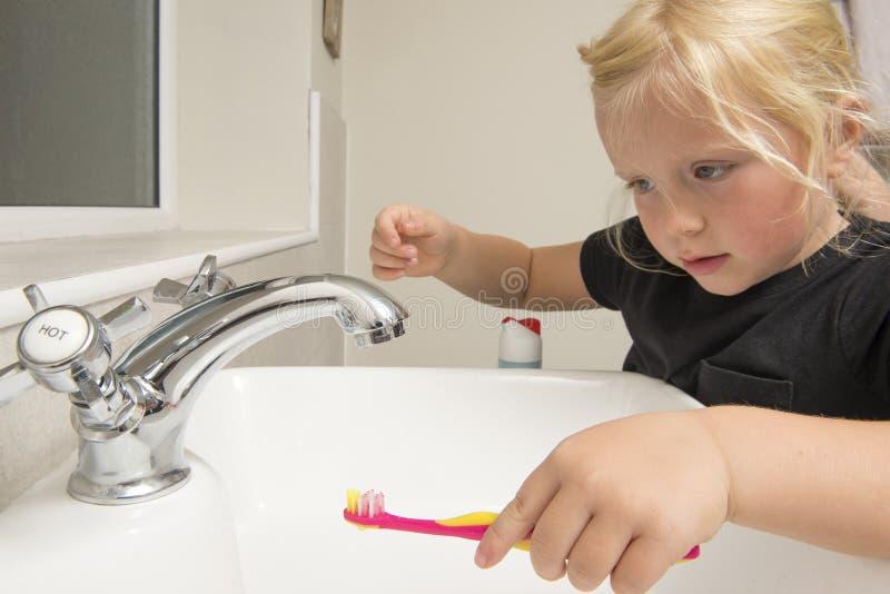 在自来水下的小女孩洗涤的牙刷在卫生间S里 免版税库存照片