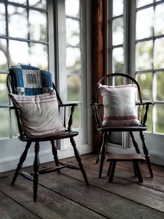 在自然光沐浴的殖民地家庭设置的葡萄酒椅子 免版税库存图片