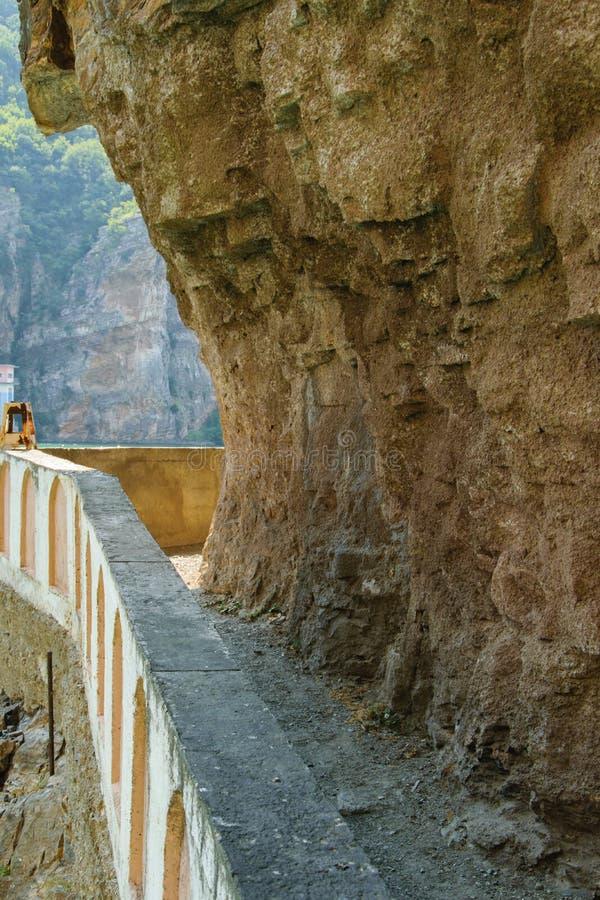 在自然岩石下的狭窄的步行路 库存图片