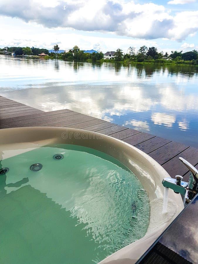 在自然河和天空蔚蓝视图旁边的露天极可意浴缸 库存图片