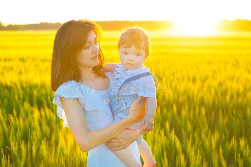 在自然照顾和户外小儿子的愉快的家庭 库存图片
