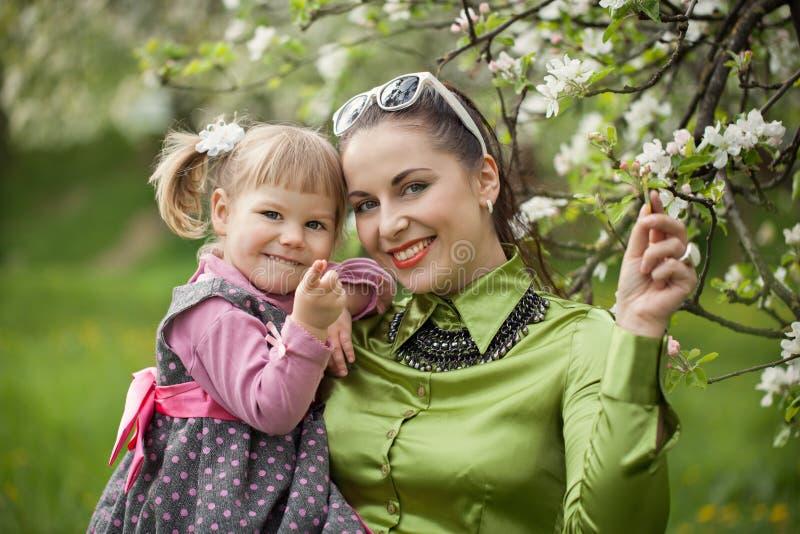 在自然照顾和户外小女儿的愉快的家庭的 免版税库存照片