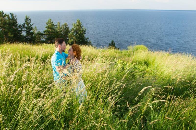 在自然的美好的夫妇在与大湖的大草 拥抱在河河岸的年轻夫妇  免版税库存图片