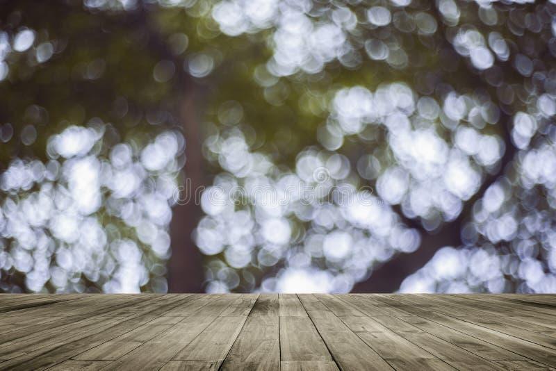 在自然被弄脏的背景前面的木板空的桌 在树bokeh的透视棕色木头  免版税库存图片