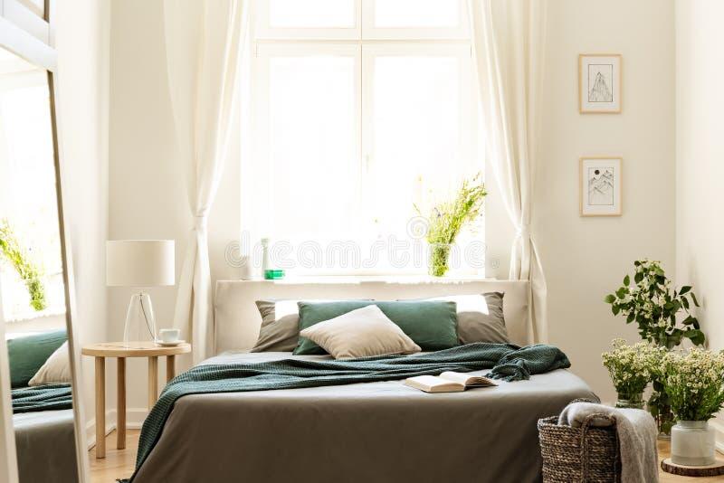 在自然颜色的卧室内部与大床、灰色和绿色亚麻布和枕头、新鲜的草甸花和一个晴朗的窗口在b 免版税库存照片