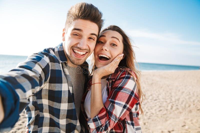 在自由供选择的假期野营的作为selfie的震惊年轻爱恋的夫妇外部由照相机 库存图片