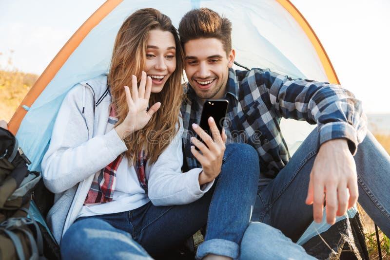 在自由供选择的假期野营的谈话的愉快的年轻爱恋的夫妇外部通过手机挥动 免版税库存照片