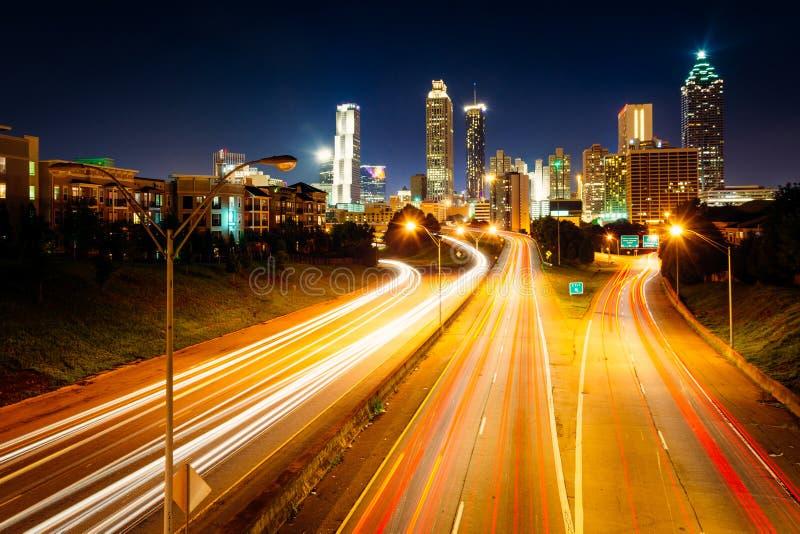 在自由大路的交通和亚特兰大地平线在晚上,看见 库存图片