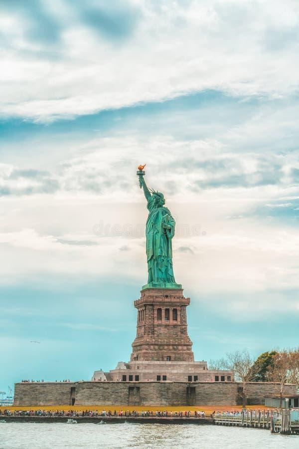 在自由岛的纽约自由女神像反对多云天空蔚蓝背景 复制空间,爱国心,旅行概念 ver 免版税库存照片