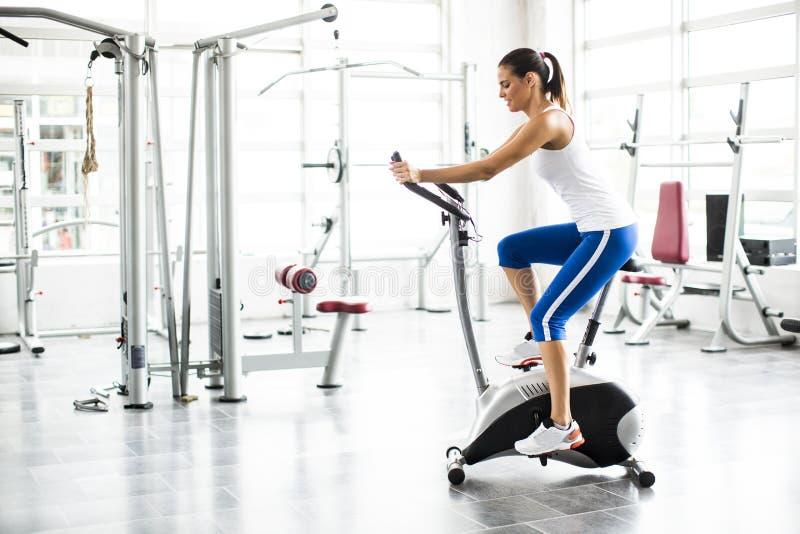 在自行车健身房的有氧运动转动的妇女锻炼锻炼 免版税库存图片