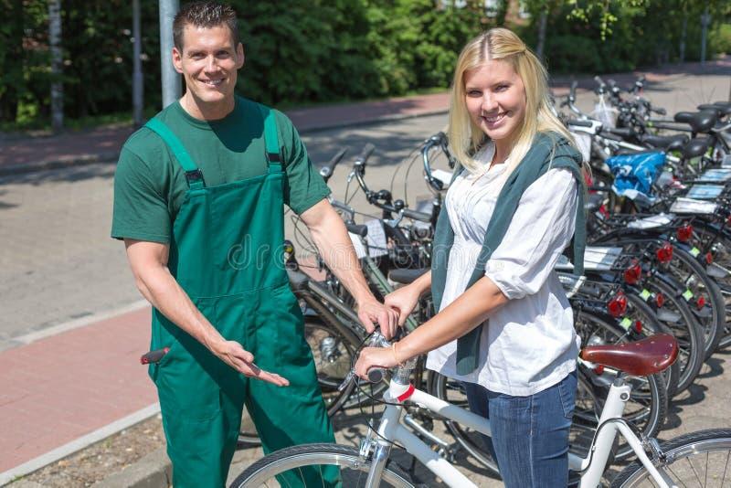 在自行车商店咨询顾客的自行车技工 免版税库存图片