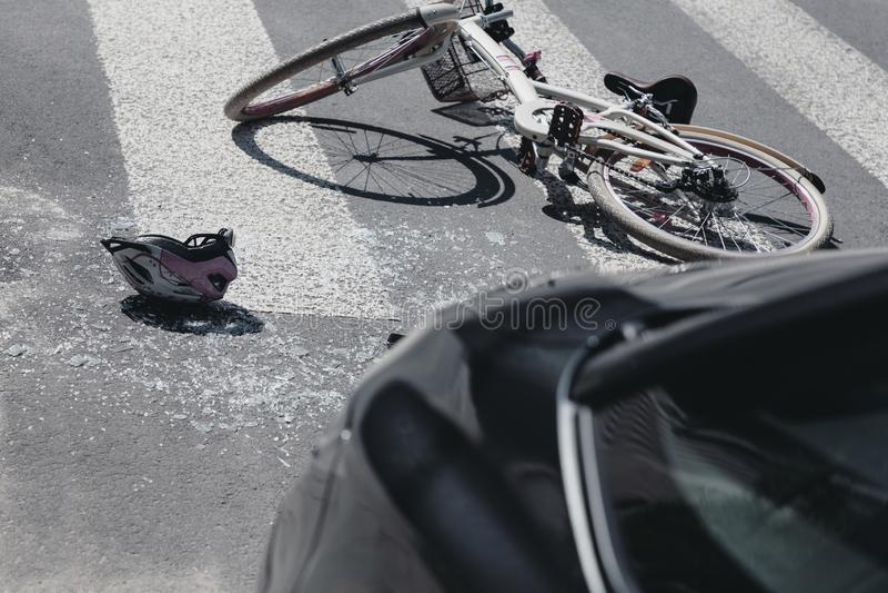 在自行车旁边的盔甲在碰撞以后的行人穿越道与汽车 免版税库存照片