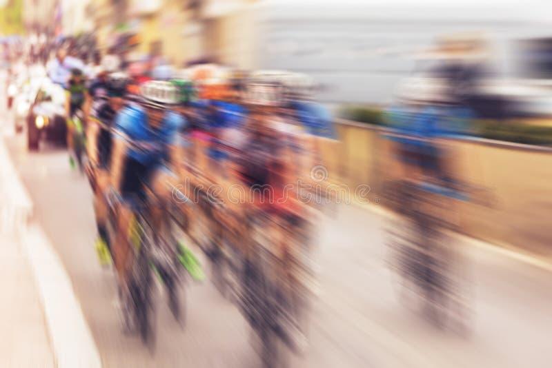 在自行车期间的骑自行车的人在城市街道,辐形上赛跑被弄脏的徒升与 免版税库存照片