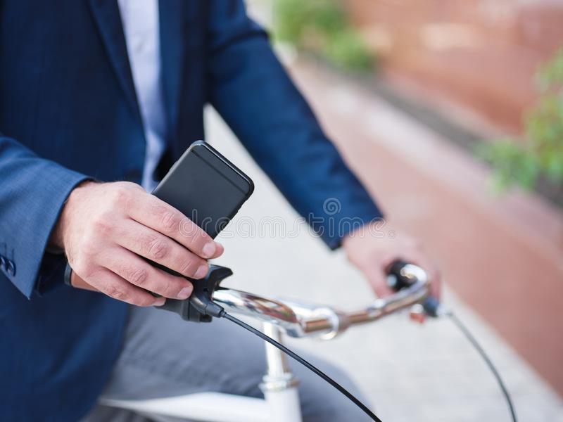 在自行车的商人,电话特写镜头用他的手 免版税库存图片