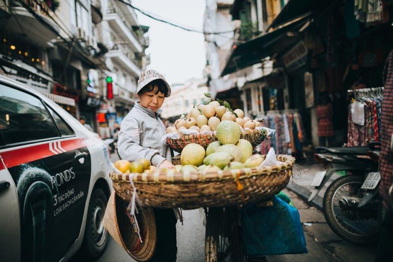 在自行车的妇女运载的果子在拥挤的街上在河内,越南 免版税库存图片