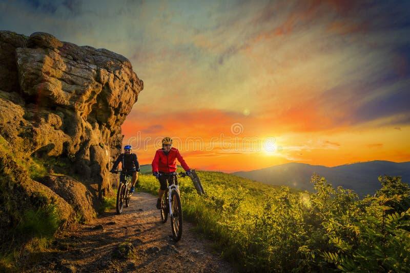 在自行车的山骑自行车的妇女和人骑马在日落山 免版税库存照片