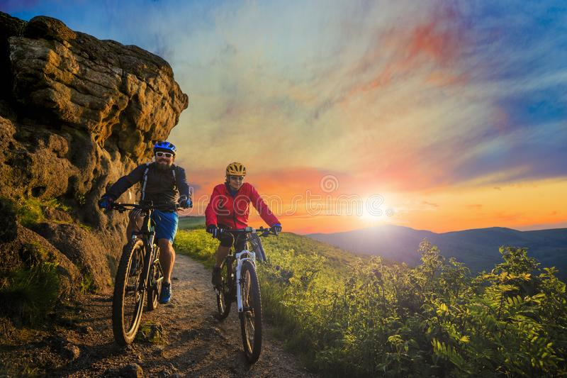 在自行车的山骑自行车的妇女和人骑马在日落山 免版税图库摄影
