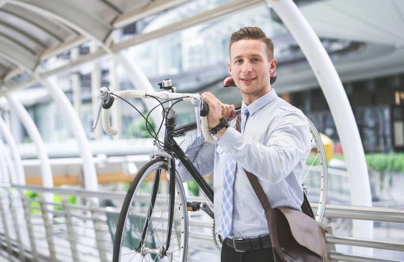 在自行车的年轻英俊的商人骑马在工作 运载他的在肩膀的自行车和看照相机的商人,当走时 图库摄影
