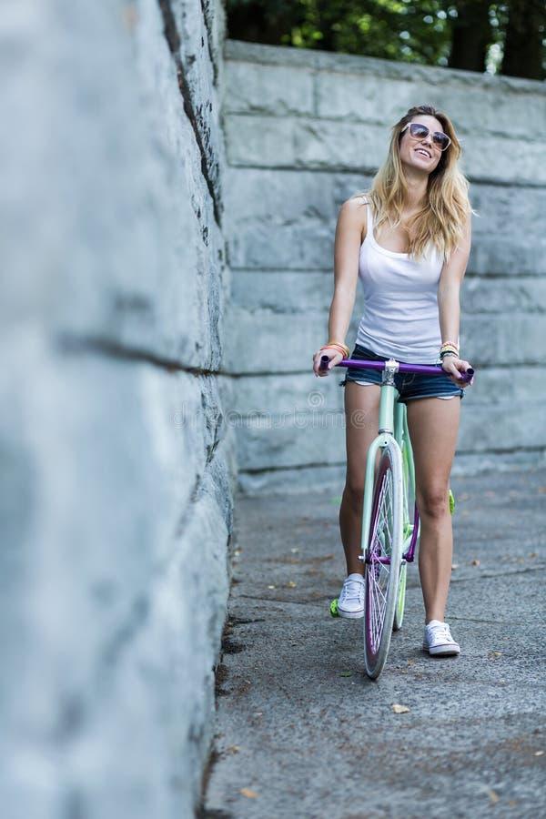 在自行车的性感的女性骑马 库存图片