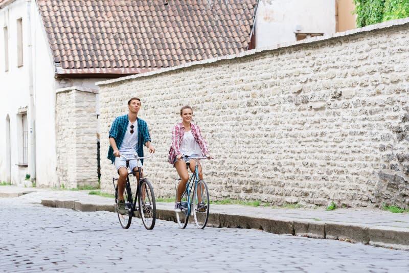 在自行车的愉快的旅行的夫妇骑马 男朋友和girlfri 免版税库存图片