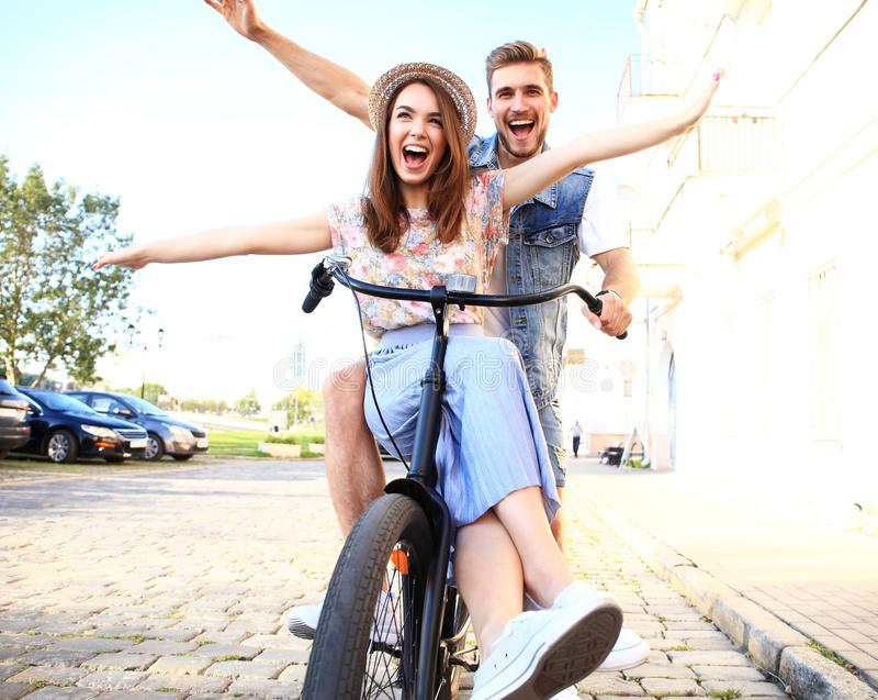 在自行车的愉快的滑稽的年轻夫妇骑马 图库摄影