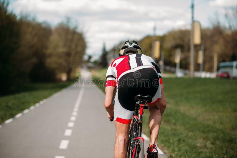 在自行车的骑自行车者乘驾,侧视图 库存图片