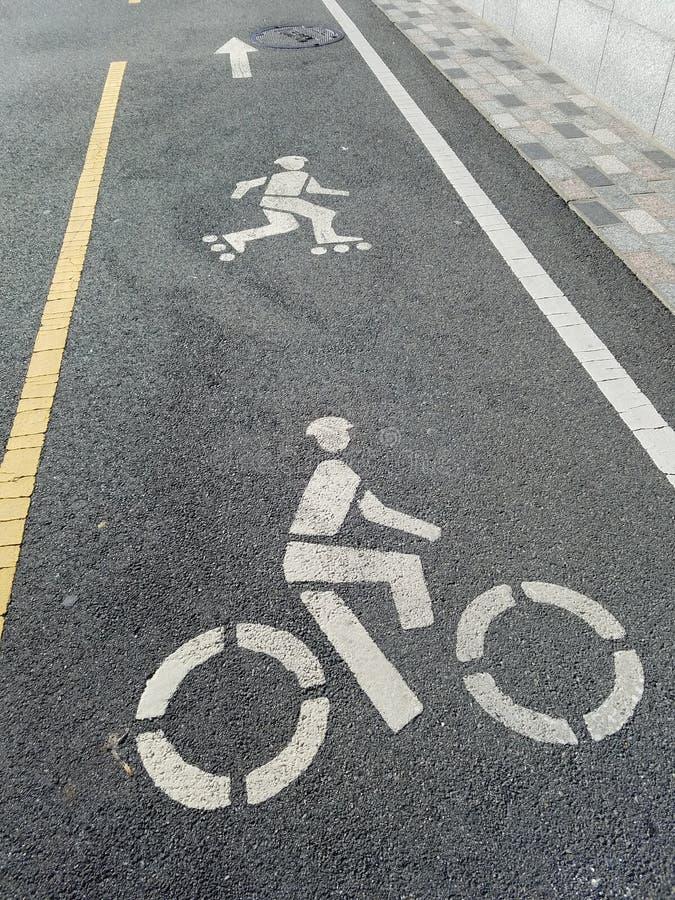 在自行车道路的滑旱冰车道,有溜冰者和骑自行车者,黄色和白色界线的显示的 免版税库存照片